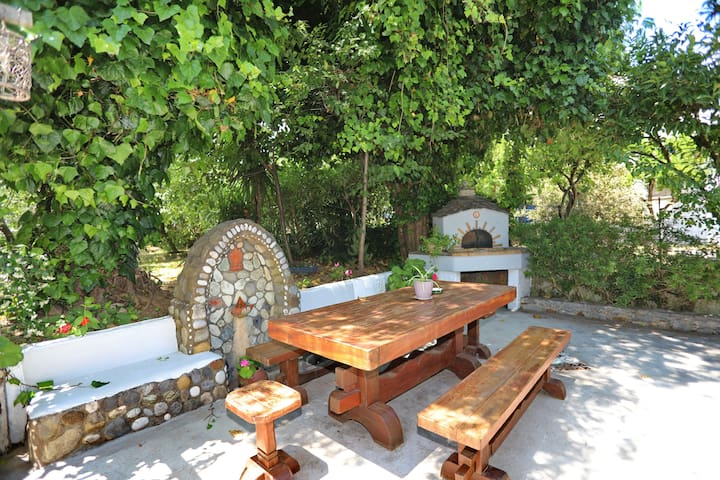 Common garden table and traditional wood-fired oven