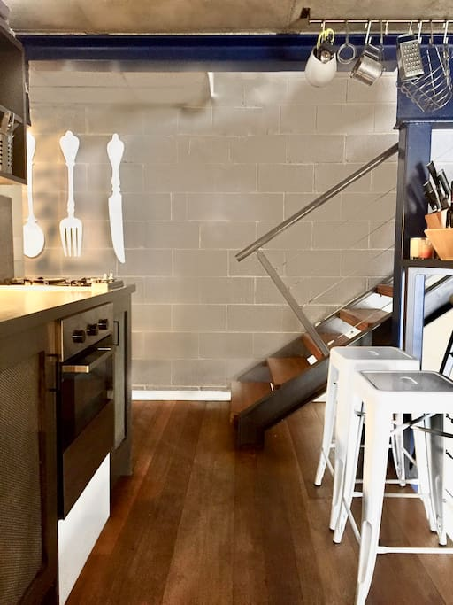 New York Style Mezzanine Kitchen with Ilve brand gas burner cooktop with modern stainless steel gas oven and refrigerator/freezer and an island bench as another option for meal preparation and casual dining area.