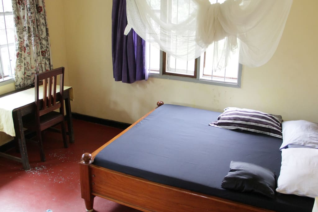 Room has large bed, windows with curtains, a mosquito net, desk and chair.