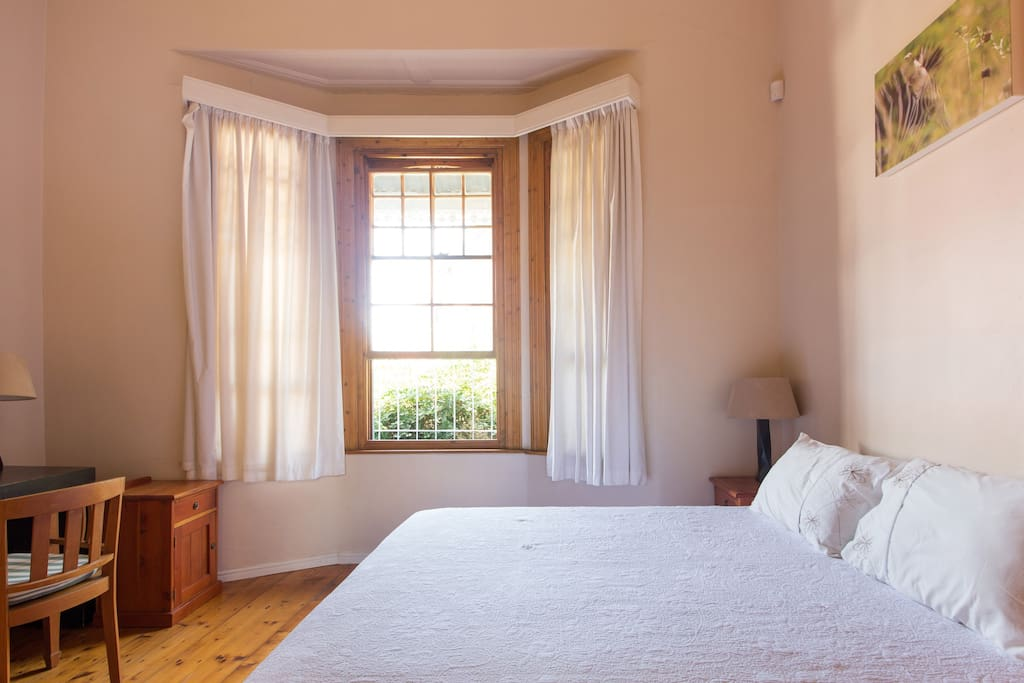 The bedroom has large bay windows and lots of natural light.