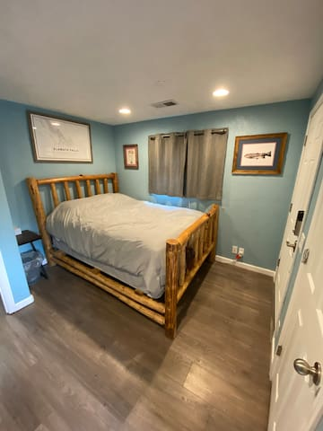 This is the master bedroom. It includes a queen bed, a door out to the deck, and an attached private full bathroom with shower and tub.