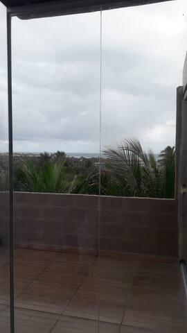 Toillete com parede de vidro e vista mar e dunnas