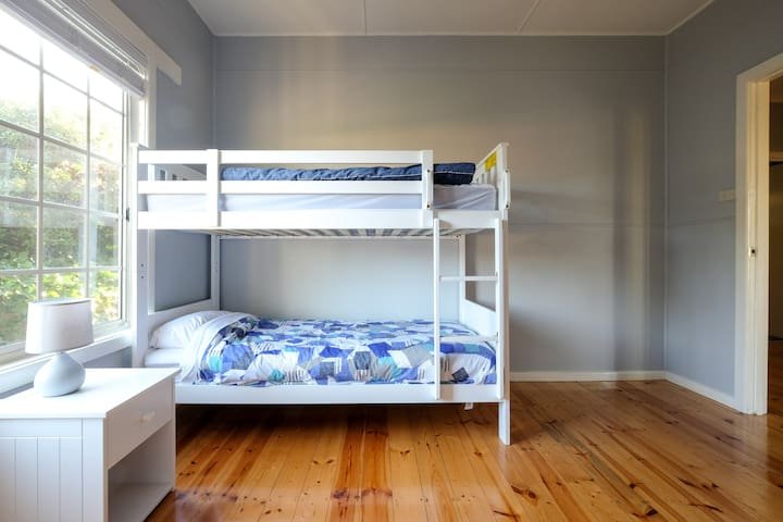 The second bedroom features a bunk bed, tallboy and wardrobes