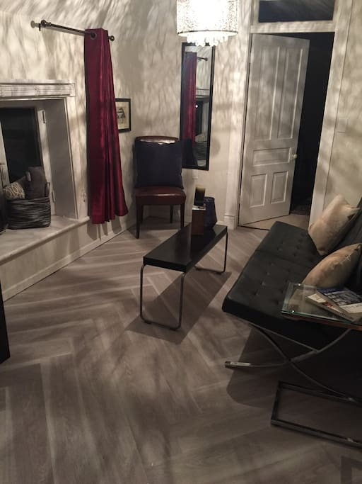 New herringbone wood plank floor in living area giving classic old world elegance to the cozy living space. Living area is compact but comfortably furnished for visitors.