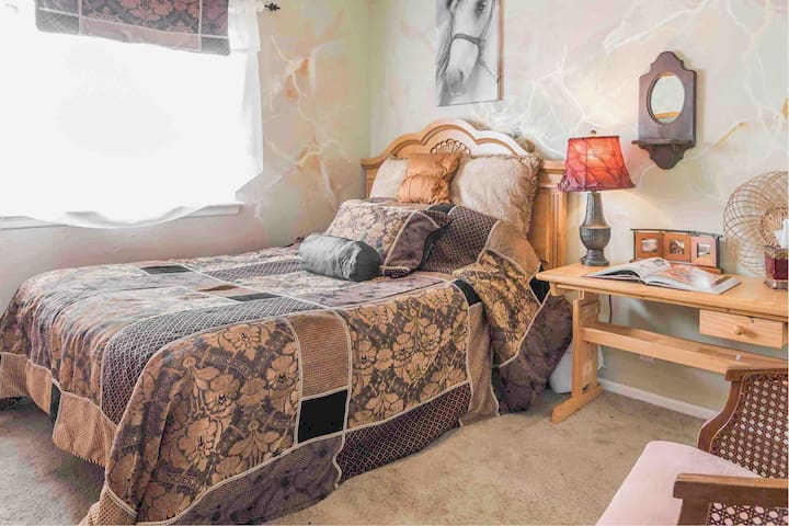 Cozy Comfort~  This comfy bed has fine new bed linens and 4 new specialty pillows.  Also offered are some unique amenities including a clothing steamer, iron and board, clock & a mini fridge (stocked for 50.+), and a Sanyo tv with Netflix.  (+a gift)