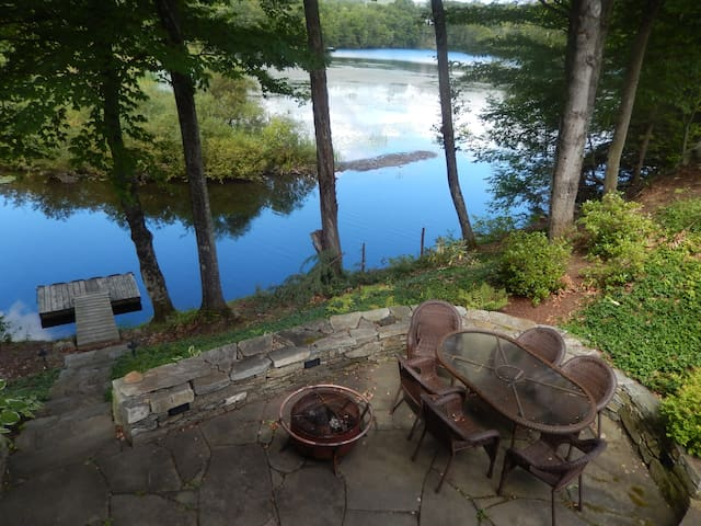 Backyard patio in quiet setting with fire pit and dock to the water