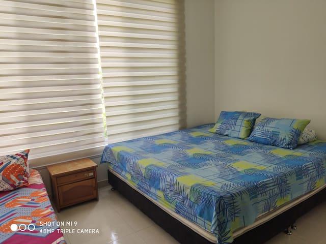 Habitación principal con baño privado cama king (2x2) mas cama sencilla.   Ventilador fijado en la pared con control remoto. Closet con Smart Tv.