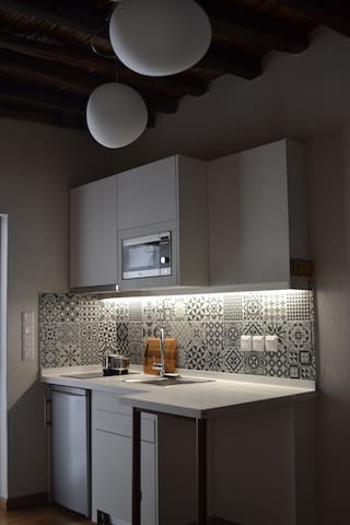 Kitchen with electric hob, microwave and fridge