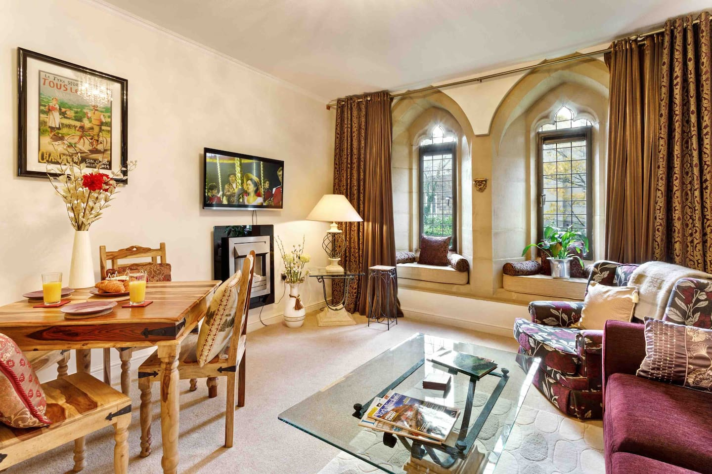 Spacious living area with TV/DVD, two window seats, massive original church windows, dining area and a sofabed