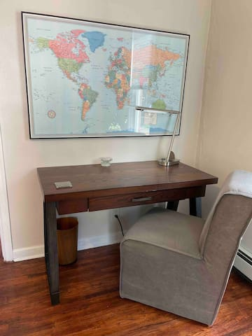 Workspace with a desk lamp that has two outlets.  The upholstered rolling chair is very comfortable!