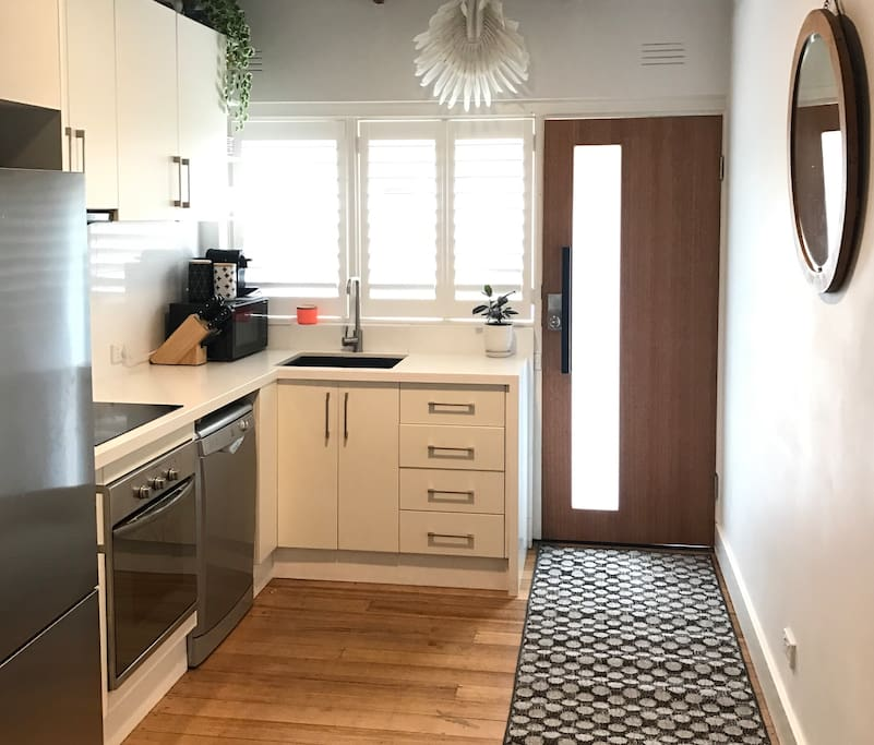 Kitchen with dishwasher, stainless steel large fridge & freezer, gas hot water, electric oven & cook top.