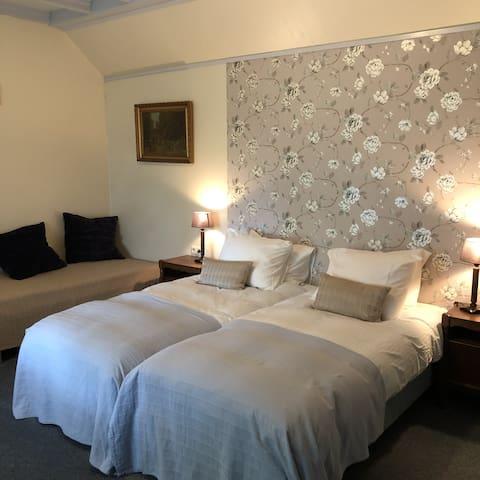 Op deze foto zijn twee bedden opgemaakt, het derde bed staat links tegen de muur.