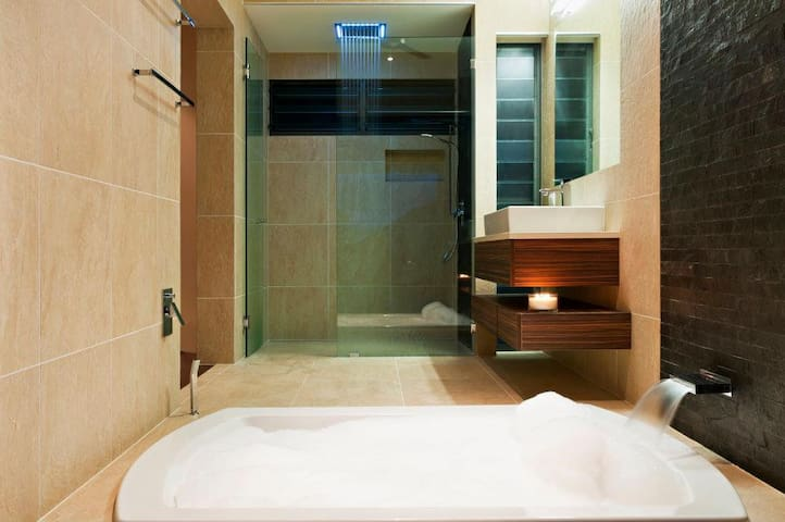 Master Bedroom ensuite with a gorgeous led light rain shower, an extra large sumptuous bath; and beautiful views towards the ocean.