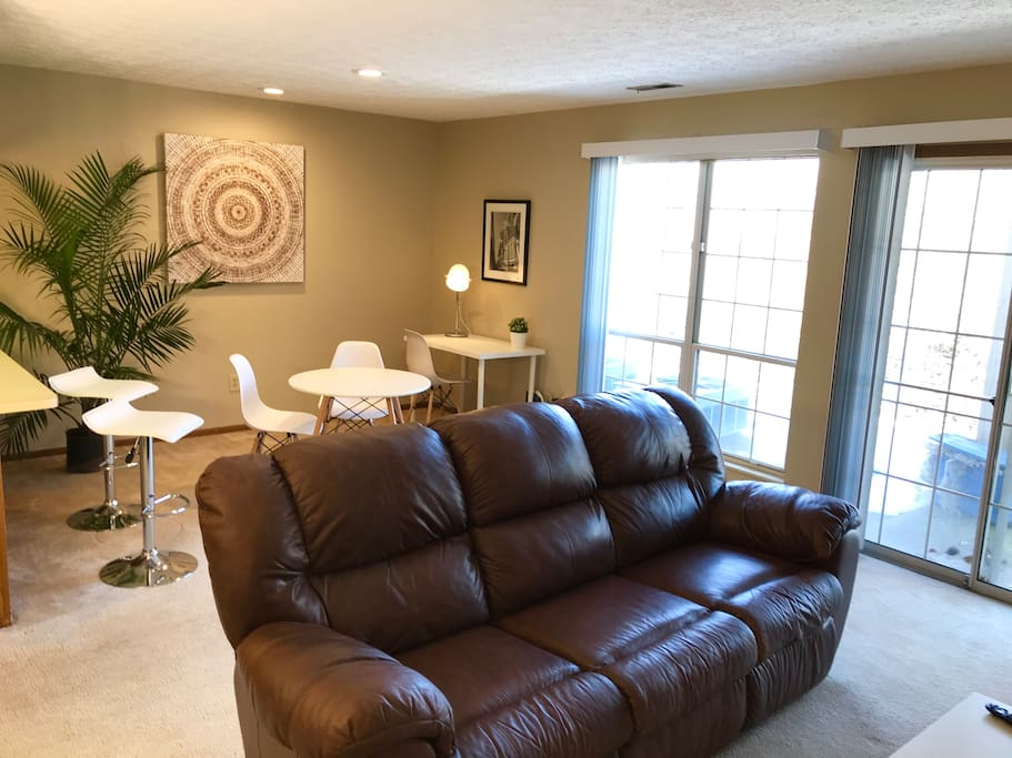 Open concept living room with light-filled windows overlooking private patio, comfy leather couch, dining area, and a desk with super fast WiFi internet.