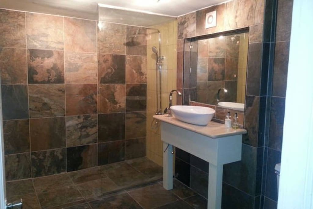 Shared natural slate tiled shower room.