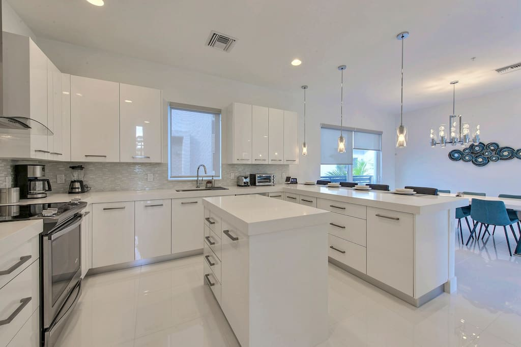 The chef's kitchen is glossy with stainless steel appliances and white cabinetry