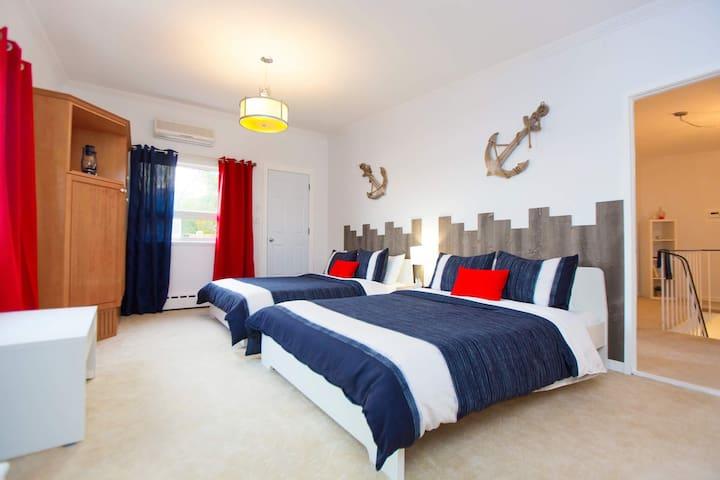 Chambre 2 lits Queen avec foyer électrique avec vue sur le fleuve. Grande penderie et salle de bain avec bain-douche