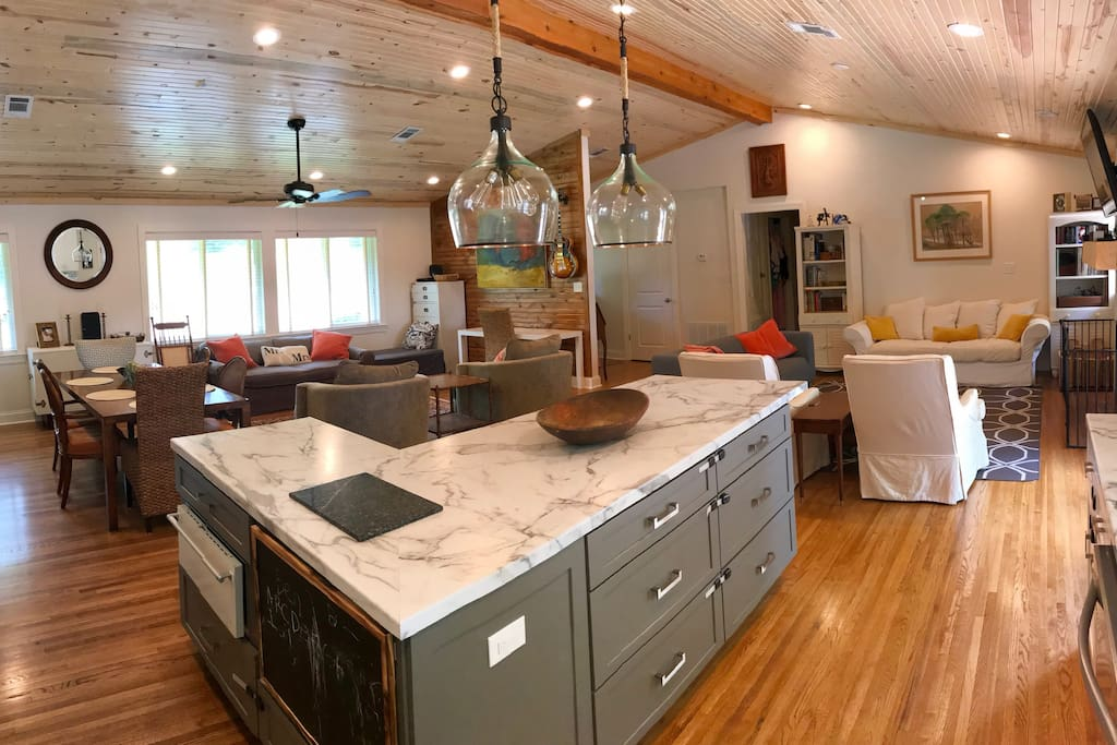 Spacious open floor plane with living room, 2nd sitting area, dining table, wet bar, and kitchen.