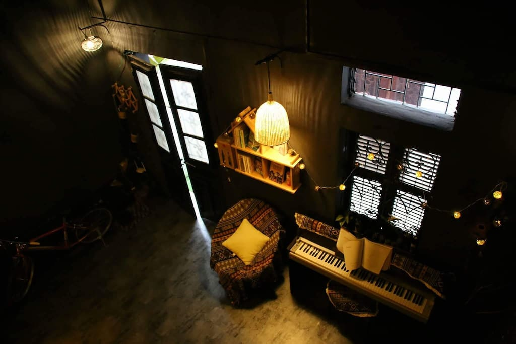 The entertainment corner with a bookshelf and a piano beside the window.