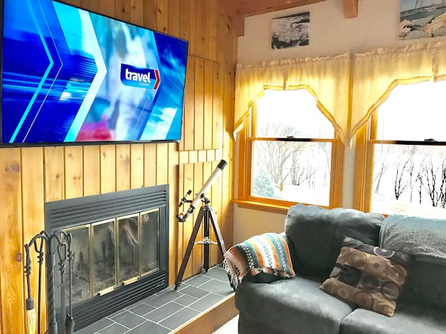 "Living room with vaulted ceiling, 60"" TV, couch, recliner, three large lake view windows"