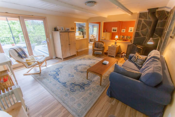 Cozy, comfortable living room area has wood stove and TV/DVD player