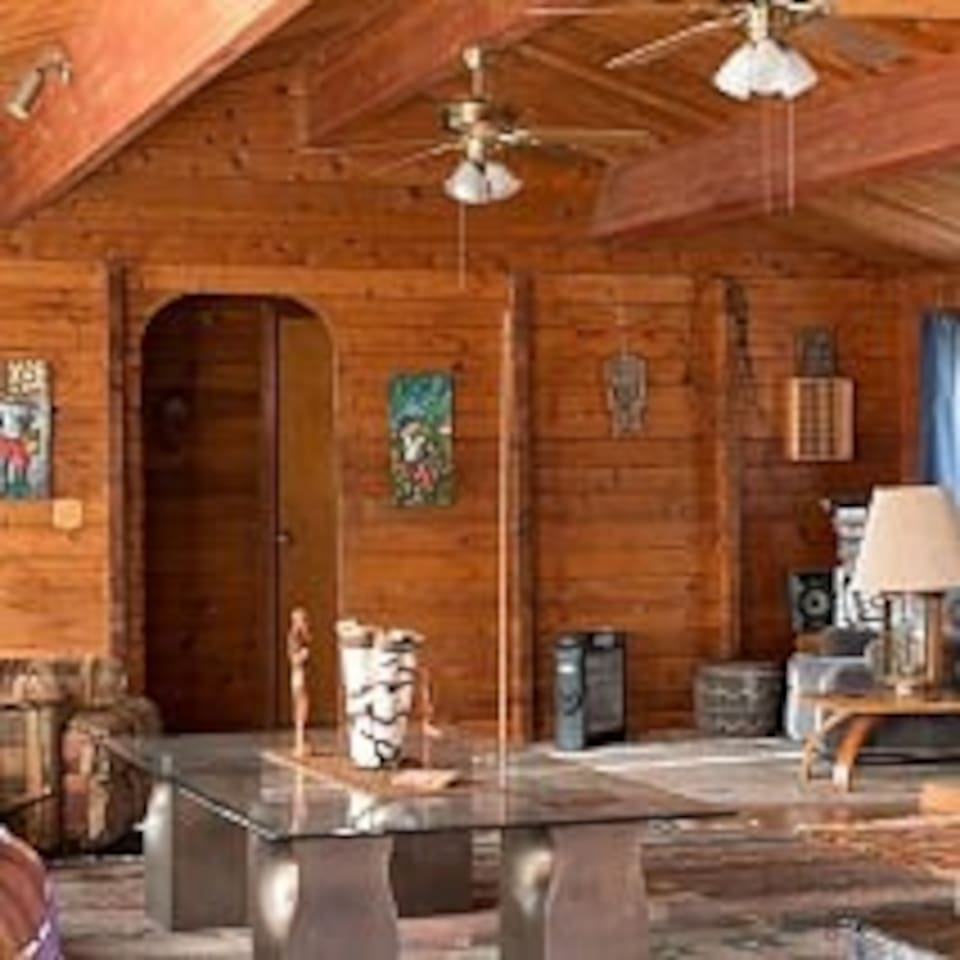 Living room is all wood with new bamboo floor and decorated with African masks,colorful rugs,carved wood figures, etc.