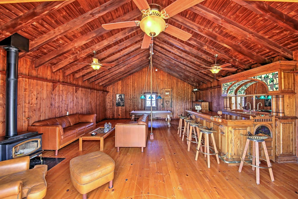 A restored barn has been converted into an entertainment room with a pool table, bar, wood-burning stove, piano, and a balcony that overlooks restaurants and vineyards.