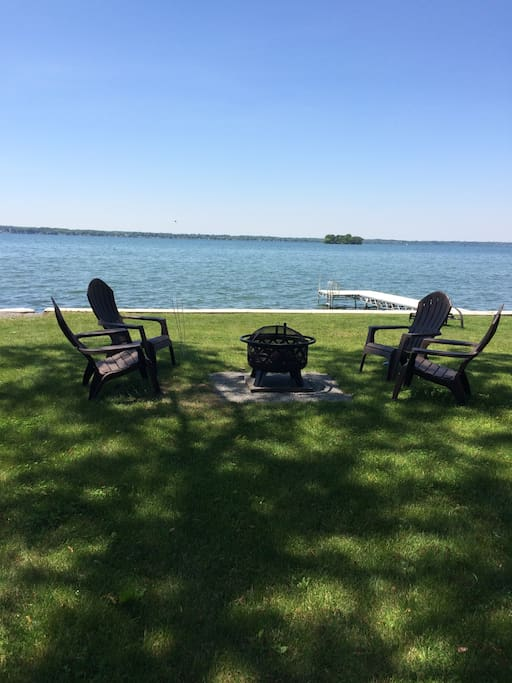 Fire pit by the lake with 6 Adirondack style chairs (only 4 shown).