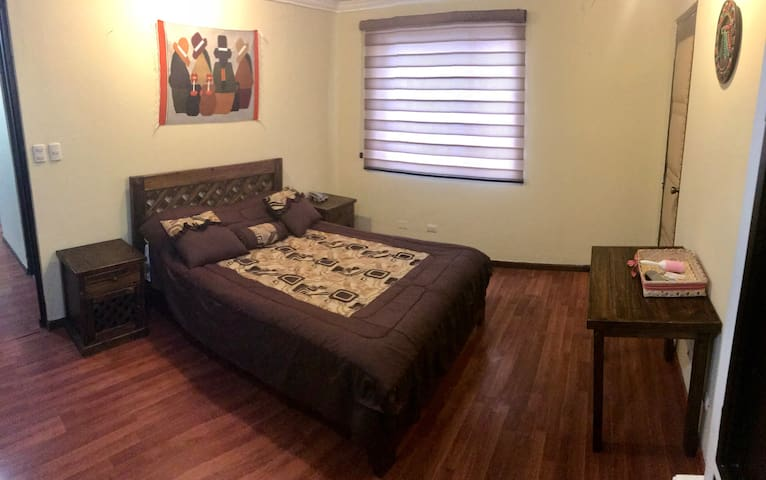 Panoramic view of the bedroom. Comfy bed, private bathroom, modern and new blinds.