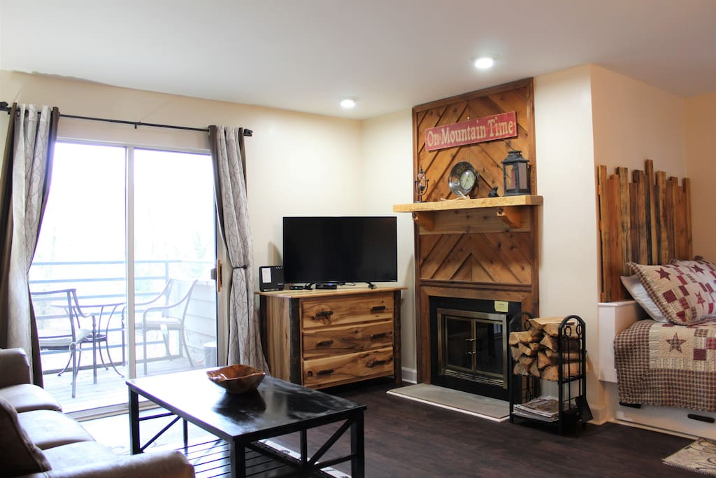 """Open floor plan: 42"""" smart TV, wood burning fireplace and dining area"""