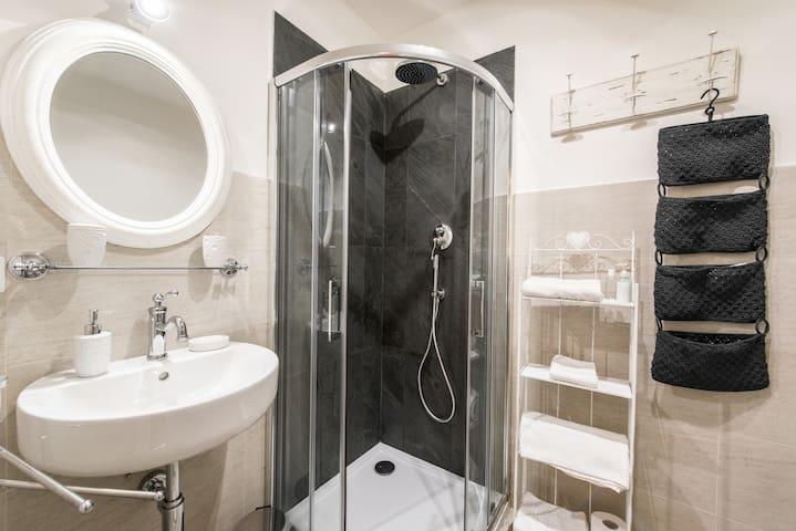 Bagno con materiali nuovi. Doccia con un soffione grande e braccetto mobile.  A disposizione sapone per le mani, phon e asciugami con tappetino.