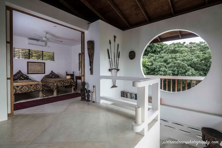 Stairs leading to the open-plan living room with fascinating art from the owner's extensive international travels.