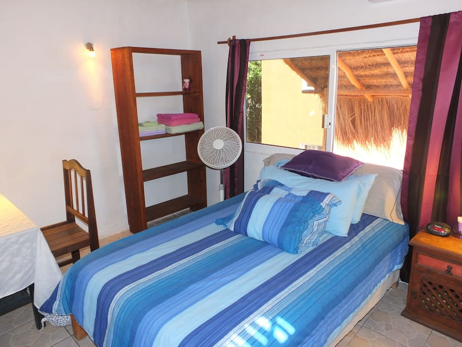 The matrimonial size bed in the apartment.  There is a nice large bay window right behind the bed.  Through the window, you can also see the new palapa that helps to keep the apartment cool during hot weather.