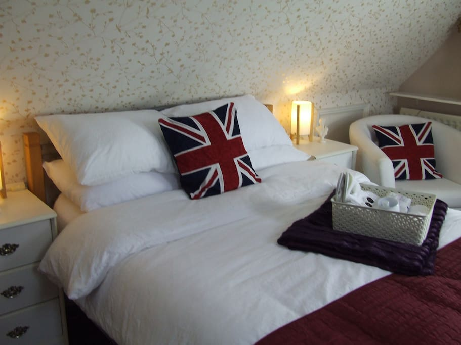 Double bed with mattress topper and Crisp White Linen.