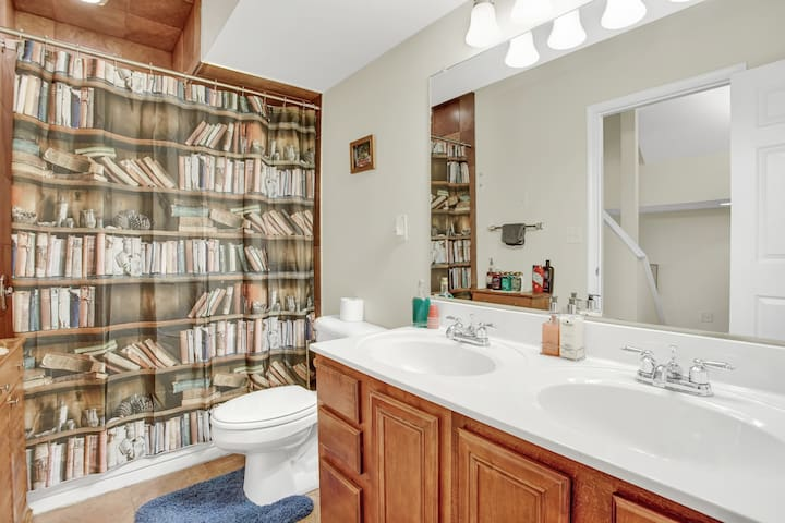 "Our spacious tile bathroom has everything you need, including great water pressure - and don't worry, that's a shower behind that ""bookshelf!""  Double sinks and an extra large mirror make it easy for couples or friends to get ready to go out!"