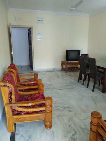 Drawing room: A spacious living area with a wooden three piece sofa set, dinning table with 6 chairs and a balcony in west facing the main road.