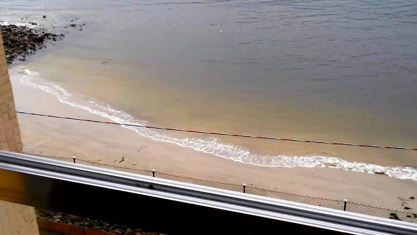 Pé na areia e vista para o mar