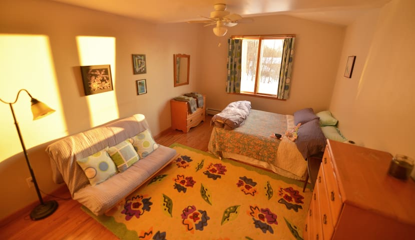 Bedroom with a queen size bed, and a futon, and an oxford comma.