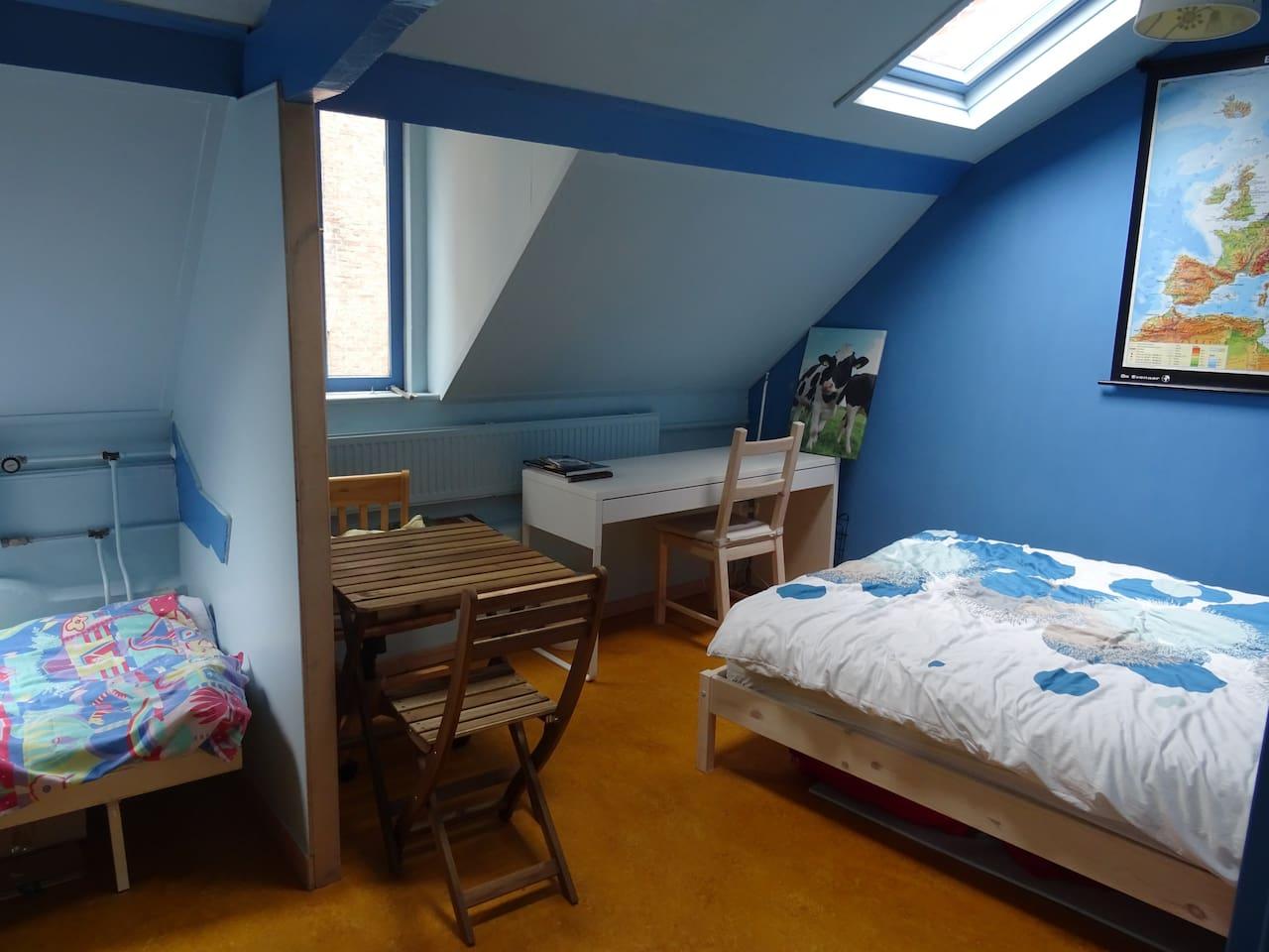 Kamer op de eerste verdieping, met schuin dak, een groot bed en een klein bed