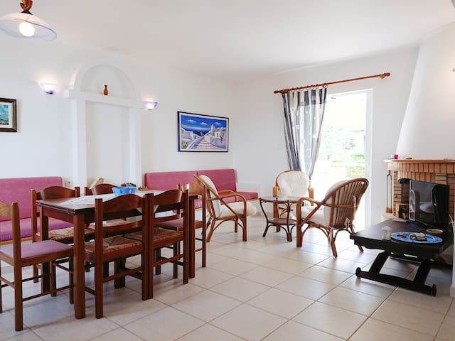 Open concept living room and dining room area with window door and private balcony and window with sea view on the opposite wall. The two comfortable built-in sofas can turn into beds.  The corner fireplace add to the coziness of the living area.