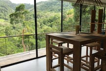 open-space dining area with solid teak wood dining table and 4 chairs