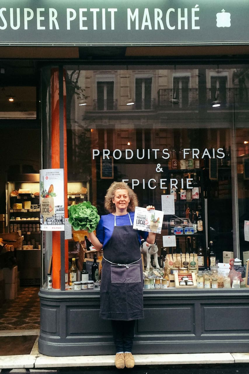 woman standing in front of a french deli