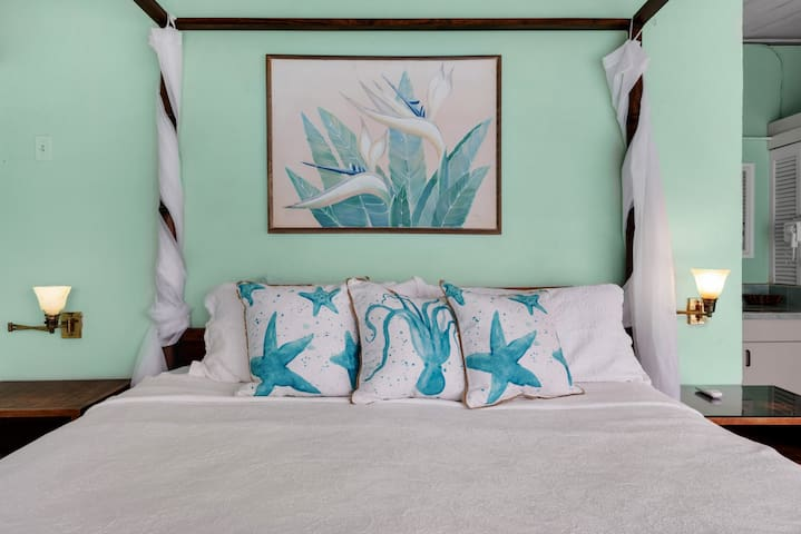 Beautiful silky starfish and octopus throw pillows tossed onto your Posturepedic king bed with romantic drapes and lighting.