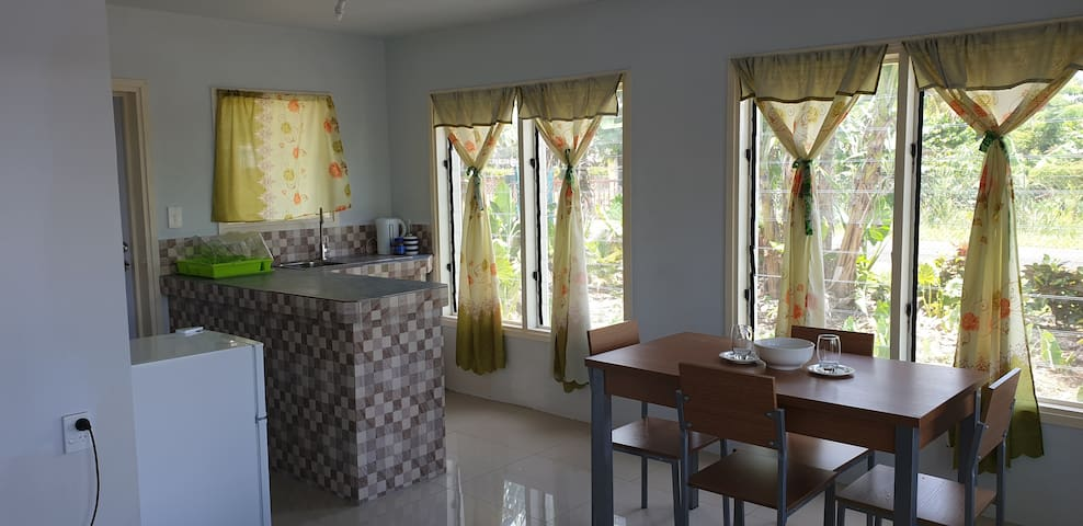 Dining table and kitchen which contains hot plates for cooking or warming up food during your stay.