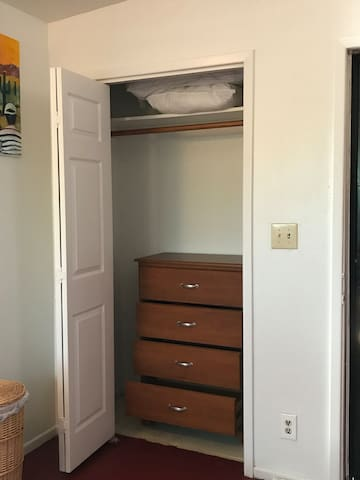Closet with hangers, dresser, extra pillows and blankets