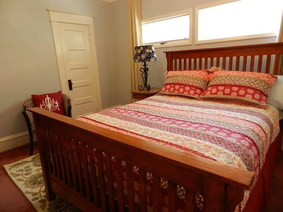 Bedroom with queen size bed, door is to private bathroom