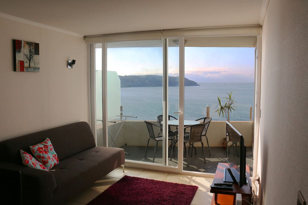 The homely and modern furnished living room with big windows and a beautiful view of the ocean and the balcony.  El acogedor living modernamente amoblado con una hermosa vista del oceano y del balcón.