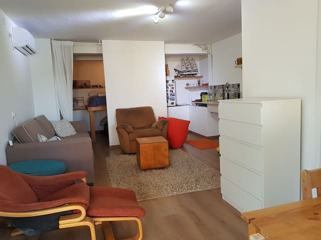 inside of the apartment on the right theres a table with three cheirs and next to it the bathroom with a shower.