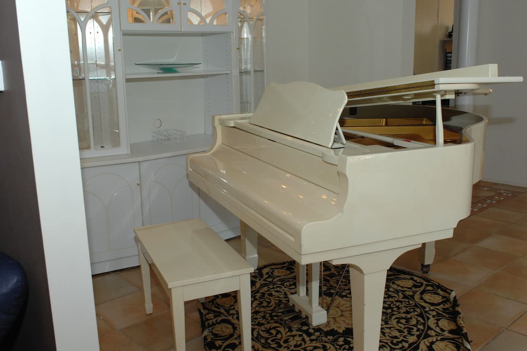 Baby grand piano, to right of hallway
