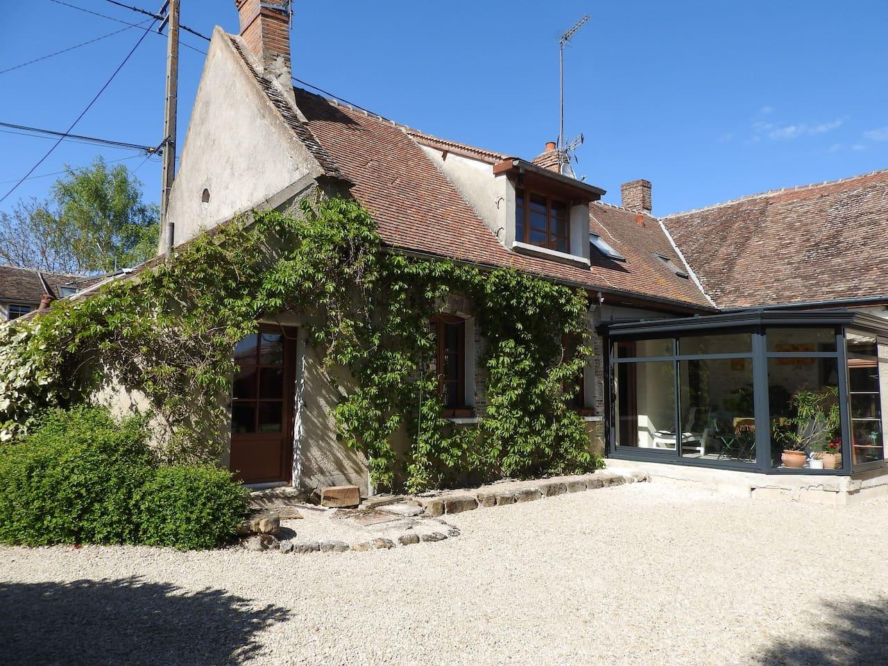 Maison traditionnelle de la Bassée avec une grande cour intérieure et une façade verdoyante dès le printemps.